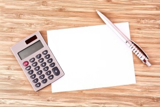 9053000-pen-een-vel-papier-en-een-rekenmachine-op-een-houten-tafel